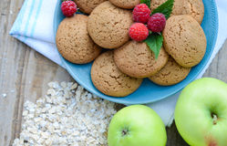 Biscotti di farina d'avena con i lamponi della bacca in una tazza delle mele verdi accanto ad un mazzo di farina d'avena dei fioc Fotografia Stock Libera da Diritti