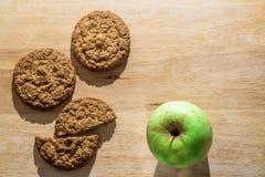 Biscotti di farina d'avena su un bordo di legno con la mela verde Fotografia Stock