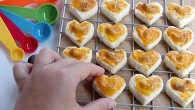 Biscotti di forma del cuore con il biscotto dell'anacardio o di Singapore e di dosatore sul fondo bianco della tavola per l'eleme video d archivio