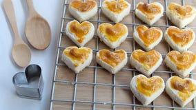 Biscotti di forma del cuore con il biscotto dell'anacardio o di Singapore ed il cucchiaio di legno sul fondo bianco della tavola  video d archivio