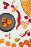 Biscotti di fortuna cinesi con i mandarini ed i talismani tradizionali isolati sul concetto bianco e cinese del nuovo anno Fotografie Stock