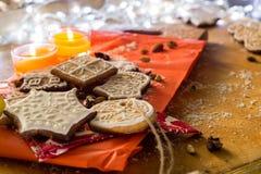 Biscotti di Natale con le candele su un fondo rosso e di legno Fotografia Stock
