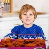 Biscotti di Natale di cottura del ragazzo del bambino a casa Immagine Stock