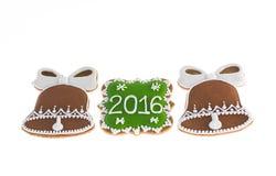 Biscotti di Natale 2016 e due campane su fondo bianco Fotografia Stock