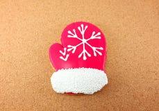 Biscotti di Natale; guanto rosso su fondo di legno Fotografia Stock