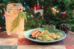 Biscotti di Natale sul piatto verde con l'albero di Natale Immagini Stock