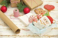 Biscotti di Natale in una scatola con i regali, le luci ed i rami dell'abete sulla tavola di legno d'annata bianca Effetto della  Fotografia Stock