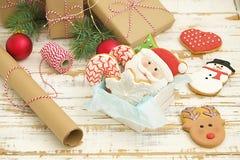 Biscotti di Natale in una scatola con i regali, le luci ed i rami dell'abete sulla tavola di legno d'annata bianca Effetto della  Immagini Stock Libere da Diritti