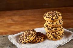 Biscotti di pepita di cioccolato impilati sul tovagliolo homespun bianco nel fuoco stile country e selettivo Immagini Stock Libere da Diritti