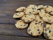 Biscotti di pepita di cioccolato casalinghi sul fondo di legno di marrone scuro Immagini Stock