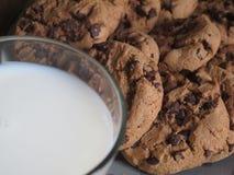 Biscotti di pepita di cioccolato e un vetro di latte immagini stock libere da diritti