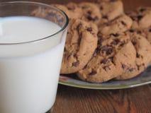 Biscotti di pepita di cioccolato e un vetro di latte fotografia stock