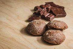 Biscotti di pepita di cioccolato impilati sul bordo di legno Fotografia Stock