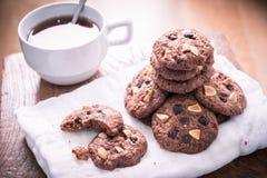 Biscotti di pepita di cioccolato sul tovagliolo e tè caldo sulla tavola di legno Immagini Stock Libere da Diritti