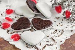 Biscotti dolci sotto forma di cuori dal cioccolato della pasta del pan di zenzero e da una glassa bianca Biscotti tradizionali Fotografie Stock