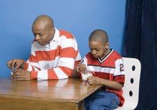Biscotti dunking del figlio e del padre fotografie stock libere da diritti