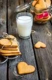 Biscotti e bicchiere di latte a forma di del cuore di giorno di biglietti di S. Valentino Fotografie Stock