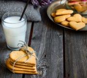 Biscotti e bicchiere di latte a forma di del cuore di giorno di biglietti di S. Valentino Fotografie Stock Libere da Diritti