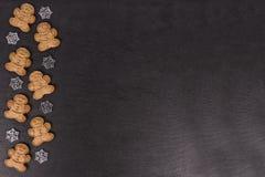 Biscotti e fiocchi di neve del pan di zenzero in decorazione sull'ardesia nel fondo immagini stock