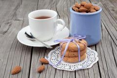 Biscotti e mandorla di pepita di cioccolato con la tazza di tè Immagini Stock