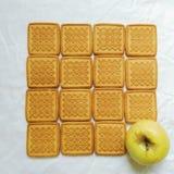 biscotti e una mela che si trova su un fondo bianco Fotografie Stock Libere da Diritti