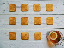biscotti e una tazza di tè con il limone su un fondo bianco Fotografie Stock