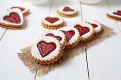 Biscotti a forma di cuore con inceppamento, dolce casalingo delizioso di sorpresa di festa su fondo di legno bianco per il giorno Immagine Stock