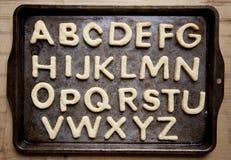 Biscotti a forma di della lettera sul vassoio di cottura Fotografia Stock Libera da Diritti