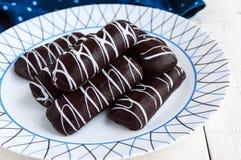Biscotti fragranti di chou in cioccolato fondente coperto di decorazione bianca su un piatto bianco su un fondo di legno immagini stock