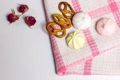 Biscotti, murhmellows, rose asciutte sulla tovaglia, foto saporita Fotografia Stock