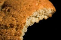 Biscotti pungenti dell'avena su una macro nera del fondo Fotografia Stock