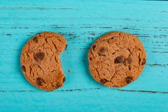 Biscotti su fondo blu ed uno con un morso fotografia stock libera da diritti