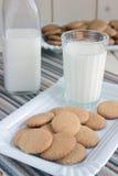 Biscotti su un piatto, un bicchiere di latte, una bottiglia di latte Fotografia Stock Libera da Diritti