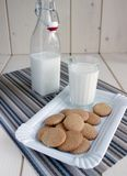 Biscotti su un piatto, un bicchiere di latte, una bottiglia di latte Immagini Stock