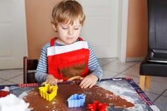 Biscotti svegli del pane dello zenzero di cottura del piccolo bambino per il Natale Fotografia Stock Libera da Diritti