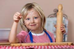 Biscotti svegli del pane dello zenzero di cottura del ragazzo Fotografia Stock Libera da Diritti
