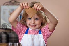 Biscotti svegli del pane dello zenzero di cottura del ragazzo immagini stock libere da diritti
