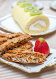 Biscotti, swiss roll and red strawberry, on fine bone china plates. Tea time. Stock Photos
