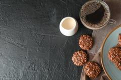 Biscotti, tazza di caffè e latte del cioccolato sulla tavola nera fotografia stock libera da diritti