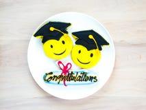 Biscotti variopinti di graduazione su un piatto bianco fotografia stock libera da diritti