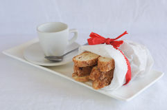 Biscotti in white paper bag on plate with coffee cup Stock Images