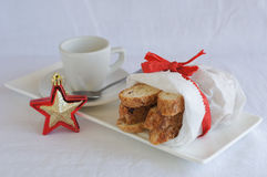 Biscotti in white paper bag on plate with coffee cup Royalty Free Stock Images