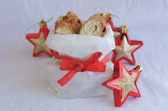 Biscotti in white paper bag on plate with red and gold stars Royalty Free Stock Photography
