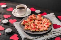 Biscotto-cuori, cuori di carta, candele, scatole con i presente e una tazza di caffè nero Fotografie Stock Libere da Diritti