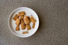 Biscotto del bambino con latte in ciotola bianca Fotografia Stock