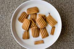Biscotto del bambino con latte in ciotola bianca Fotografia Stock Libera da Diritti