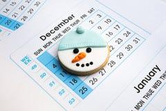 Biscotto del pupazzo di neve nel fondo di dicembre del calendario Immagini Stock Libere da Diritti