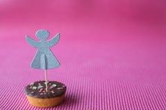 Biscotto di Natale con il cappello a cilindro decorativo di angelo su fondo rosa Fotografia Stock Libera da Diritti