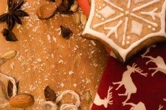 Biscotto di Natale su un fondo di legno e su un tessuto rosso Immagini Stock Libere da Diritti