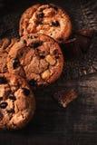 Biscotto di pepita di cioccolato su tela da imballaggio e sulla tavola di legno rustica Freshl Fotografia Stock